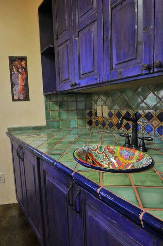 bold violet kitchen cabinets and green tiles on the backsplash and countertop