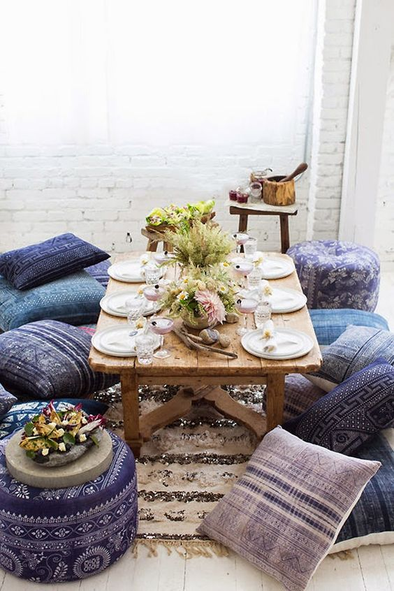 low picnic table with Moroccan styled pilows and ottomans for guests