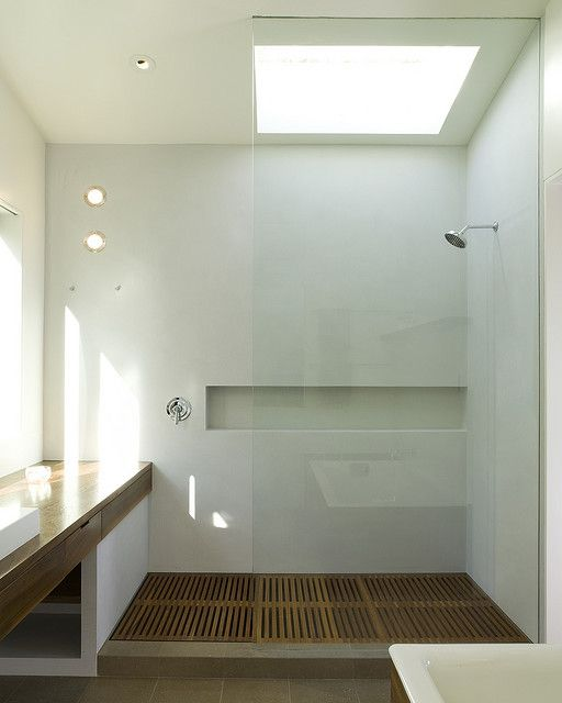 spa-like walk-in shower with a wooden floor and a built-in niche