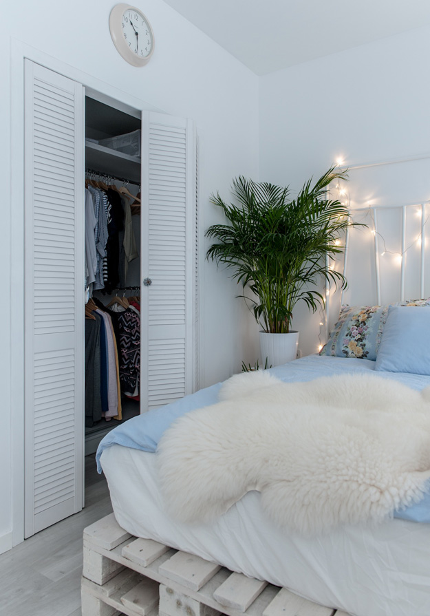 Built-in wardrobes are covered with rustic doors and fresh greenery enlivens the cold-colored space