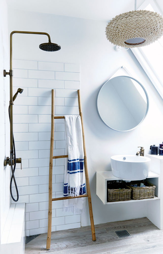 The bathroom is modern, clean and white, with wooden and rattan touches