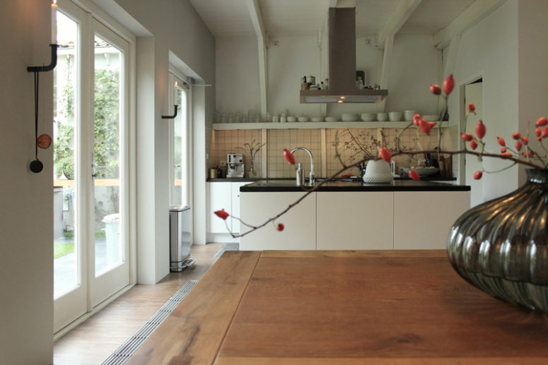 The kitchen is a modern one, with black and white cabinets and open shelving for an airy look