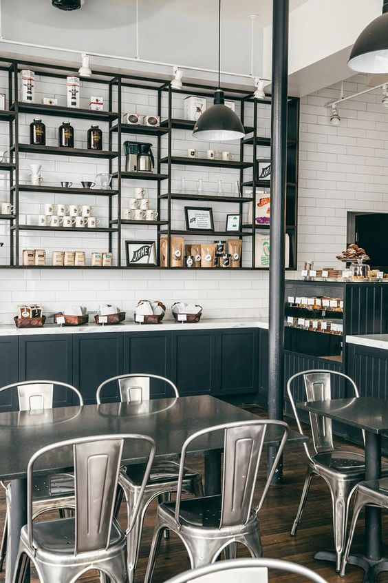 industrial-styled coffee shop with metal furniture and dark metal shelves