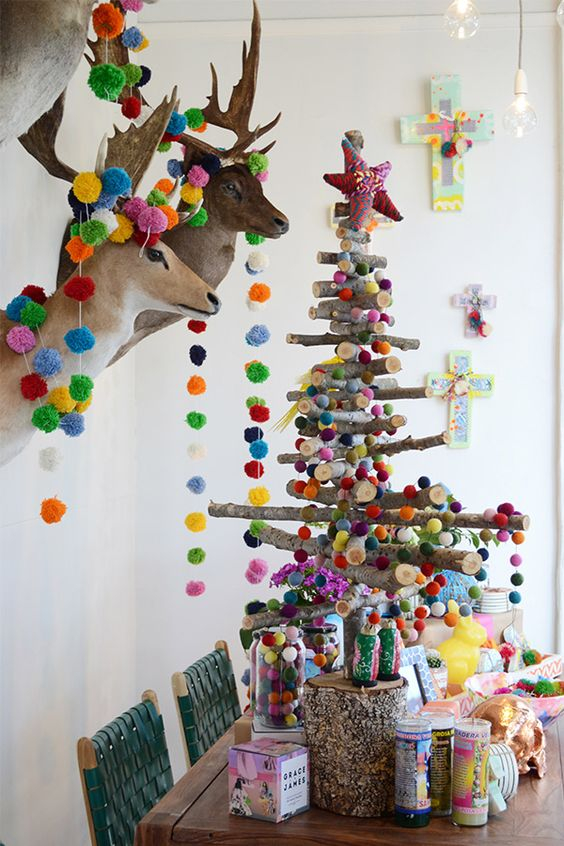 stick Christmas tree and taxidermy decorated with colorful pompoms