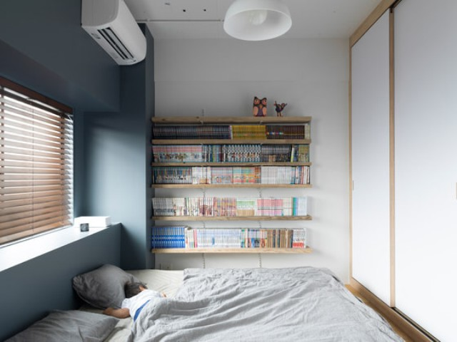 The bedroom is small and simple, with shelves and a covered window for comfortable daytime sleep