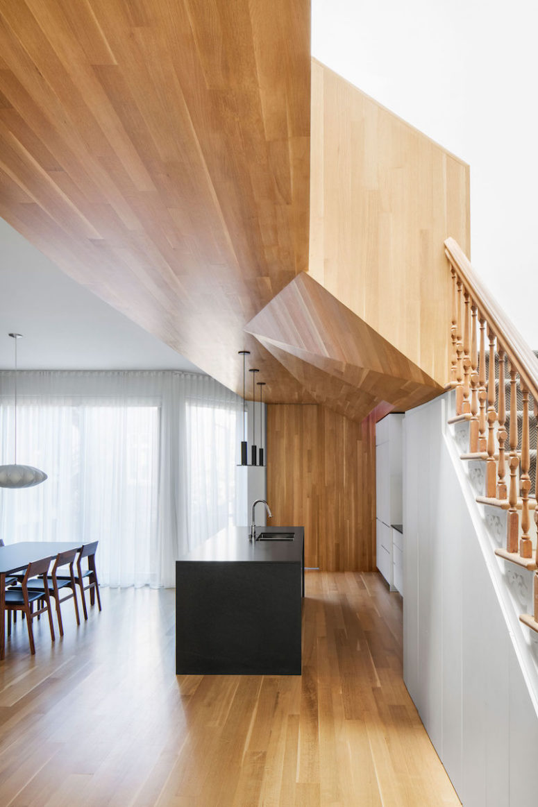 The geometrical ceiling covered with warm woods is a focal point of the kitchen and dining area