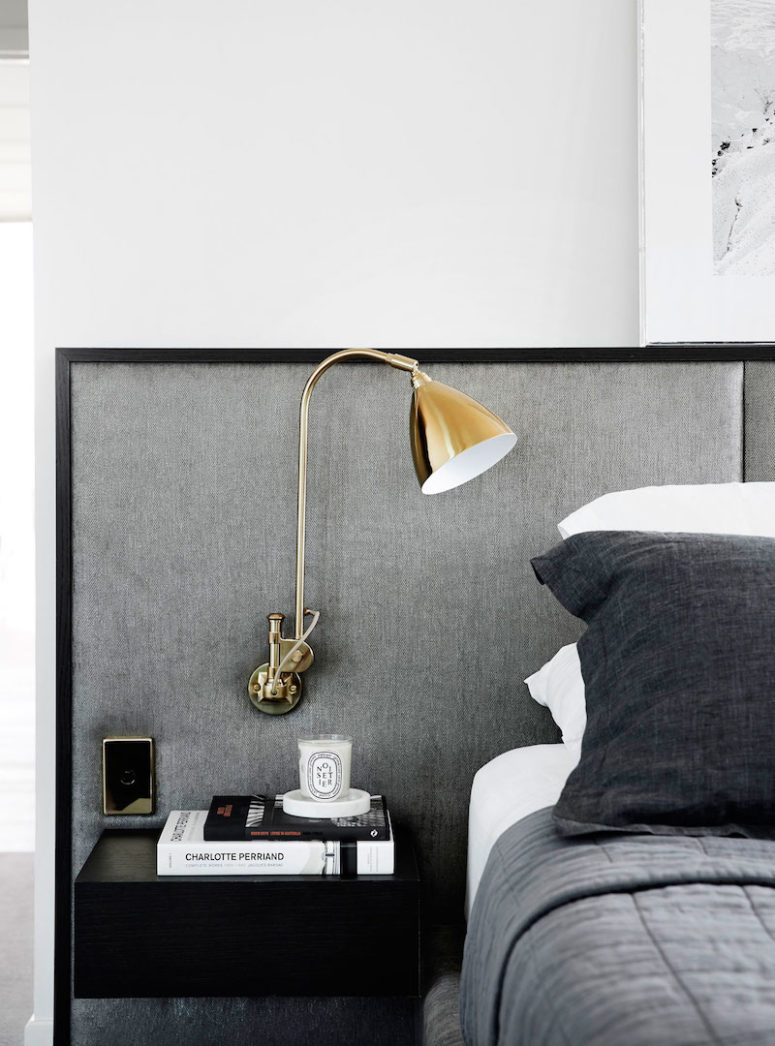 The oversized headboard has attached side tables and sconces