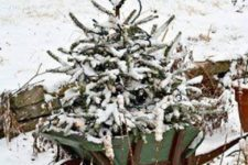 07 a snowy tree in a garden cart is a cute idea and looks natural