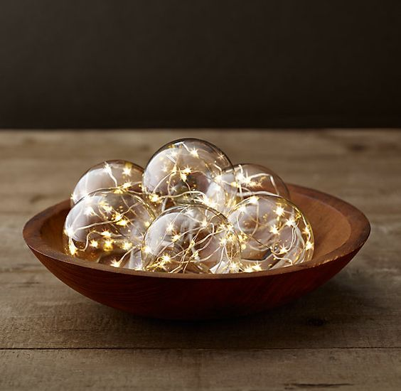 a wooden bowl with glass globes with string lights inside