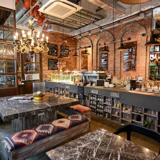 industrial interior is done with exposed pipes and brick walls, upholstered benches make it cozier