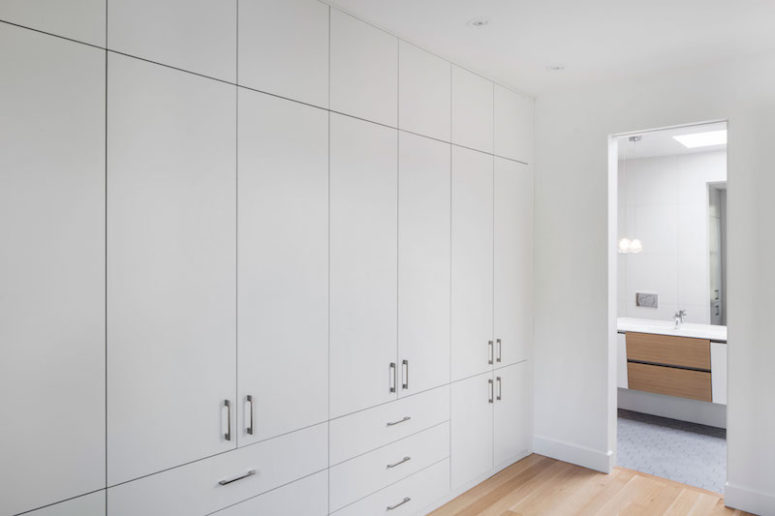 A large wall unit occupies an entire wall in the master bedroom, offering lots of storage