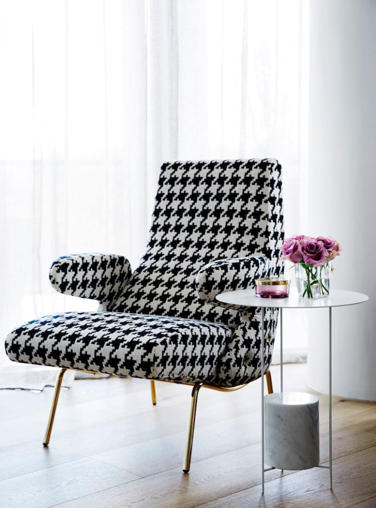 Glam accents can be seen throughout the apartment, such as this chic patterned chair