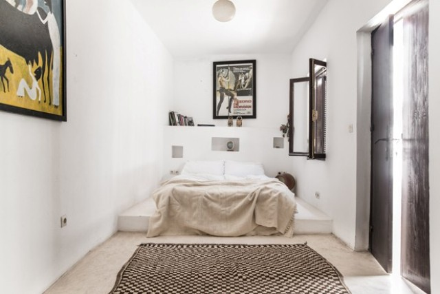 The bed in the master bedroom is placed onto a concrete platform, and an ethnic rug is a cool idea