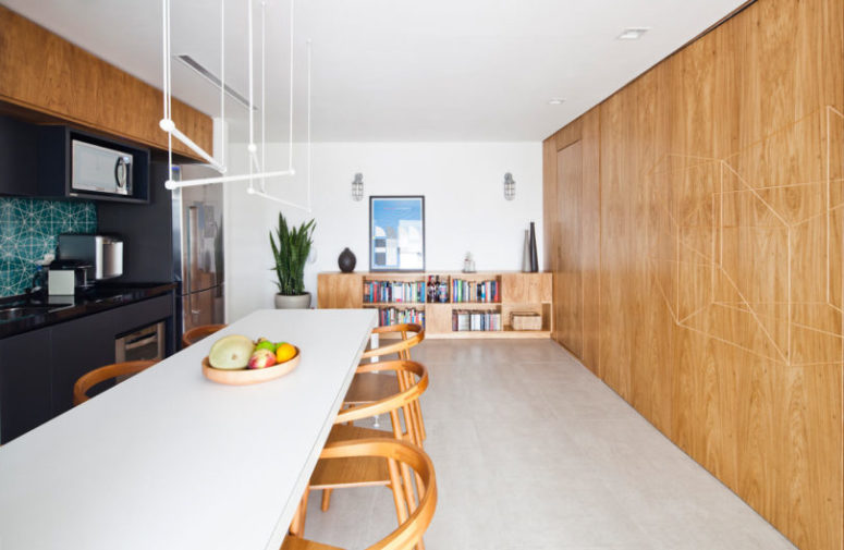 The kitchen is rather spacious, with bookshelves that echoes with a wooden panel