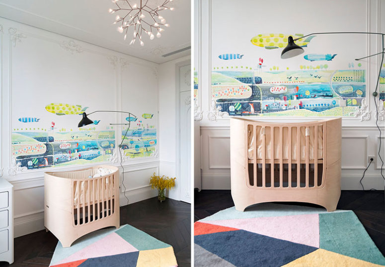 The nursery boasts of unique watercolor wall art over the crib
