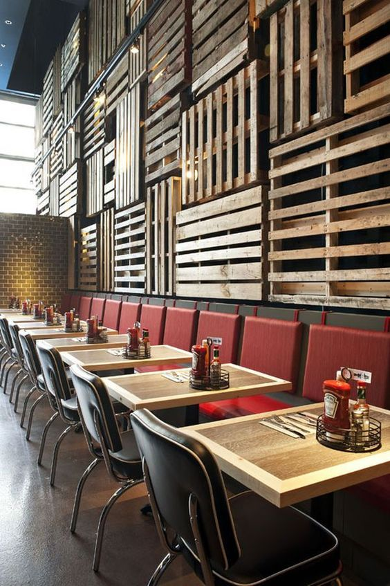pallets cover the wall and contrast with red chairs and retro tables