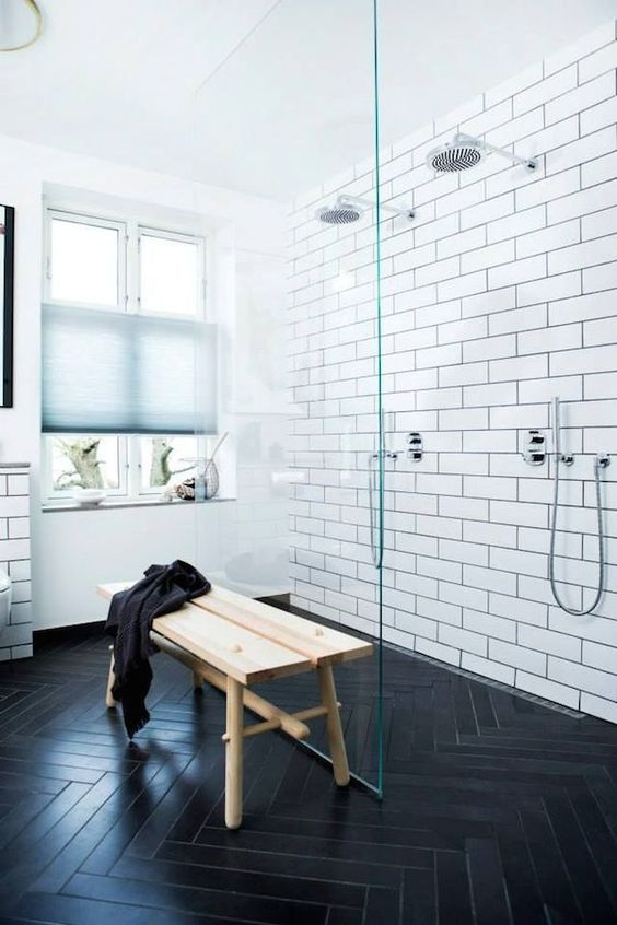 subway tiles with black grout and dark chevron-clad floors