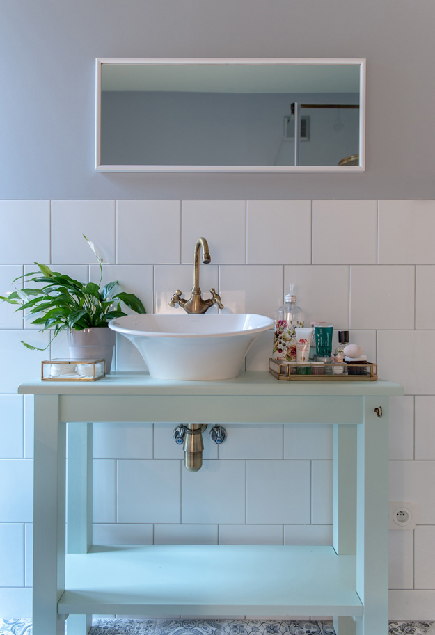 The bathroom counter is mint-colored, and gold touches make the space more refined
