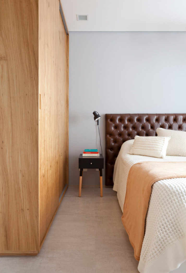 The bedroom has simple and cozy design, with a warm wood wardrobe, a leather headboard and warm-colored touches