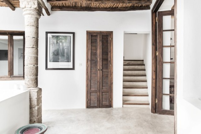 Woodwork in dark shades and lots of concrete and stone give the home a traditional yet modern look