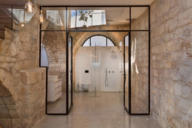 The bathroom also has frosted glass doors and the focal point is the original stone walls