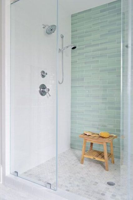glass-enclosed shower with a green tile accent wall
