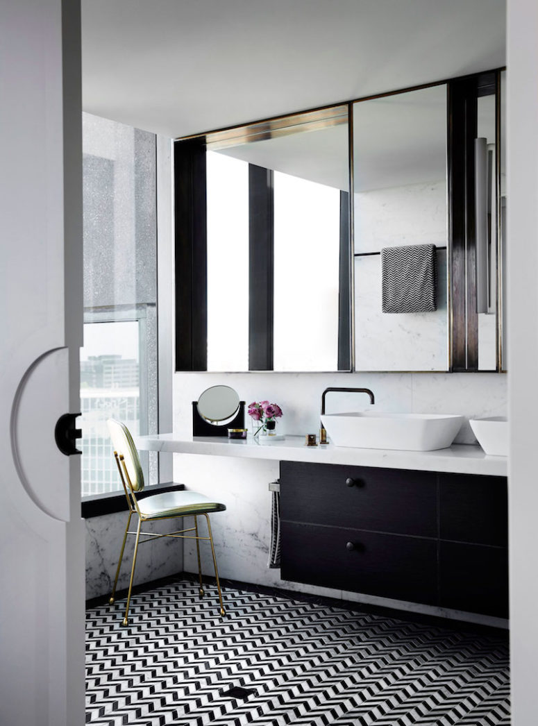 The master bathroom is decorated in tones of black and white with subtle metallic accents