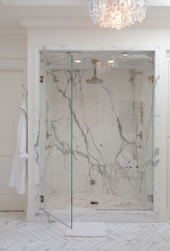 luxurious marble shower and a large crystal chandelier