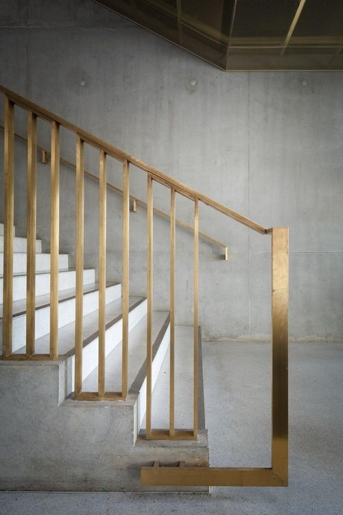 gold metallic banister on a concrete staircase look modern and chic