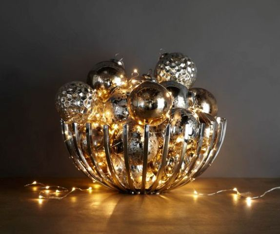 modern bowl filled with metallic ornaments and lights