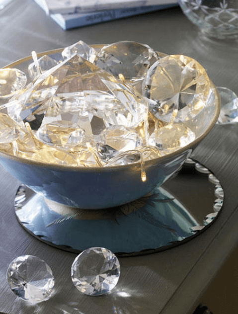 a bowl with string lights and large crystals that reflect the lights