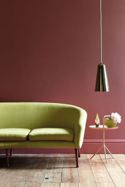 a lime green sofa looks outstanding and fresh against a burgundy wall