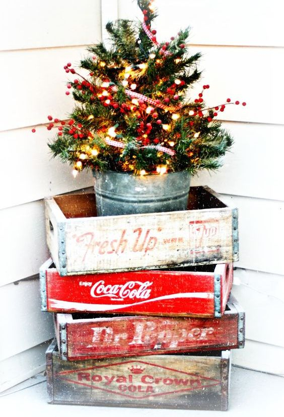a small tree with lights and berries in a glavanized bucket and crates - Small Outdoor Christmas Trees