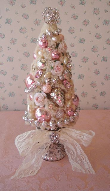 tabletop glossy ornament Christmas tree with jewelry and a lace bow