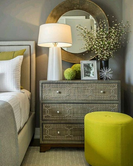 a neutral bedroom can be spruced up with greenery pillows and ottomans