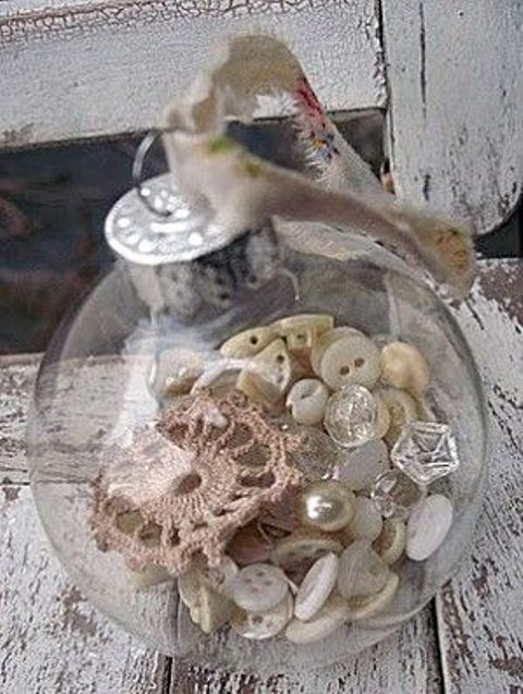 a transparent glass ornament filled with buttons, pearls and lace