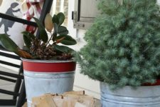 17 aged red stripe galvanized buckets with wood, greenery and an evergreen tree