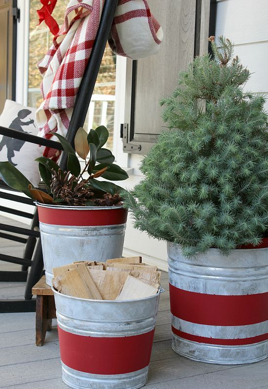 aged red stripe galvanized buckets with wood, greenery and an evergreen tree