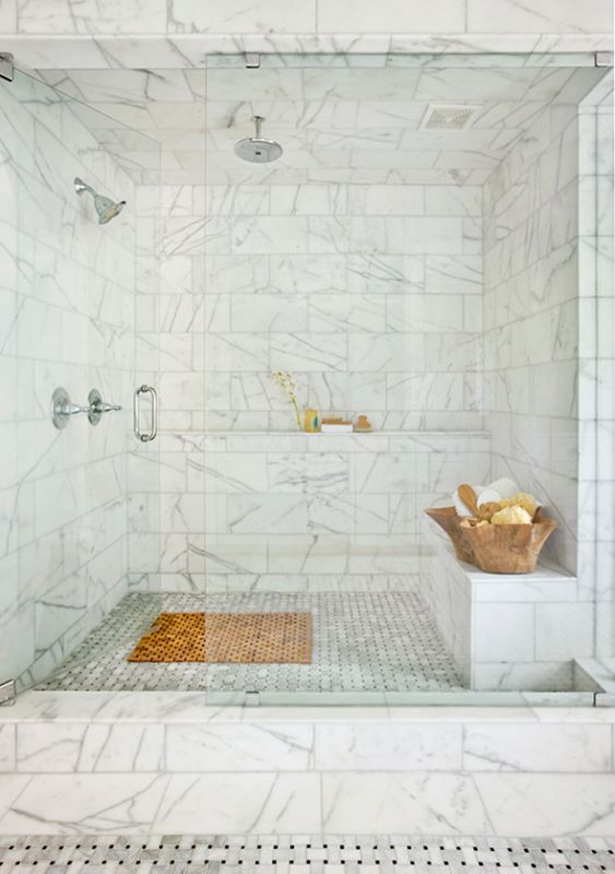 large marble shower and steam room in one with shelves and a bench