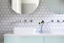 17 white hex tiles with black grout contrast with mint cabinets