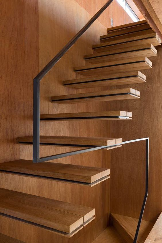 minimalist staircase with a metal handrail and no balustrade