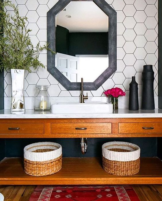 white hex tiles on the walls with black grout and a black framed mirror