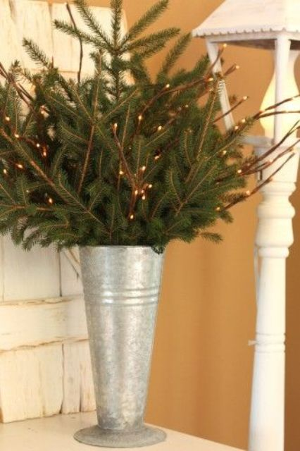 galvanized bucket with evergreen and light branches