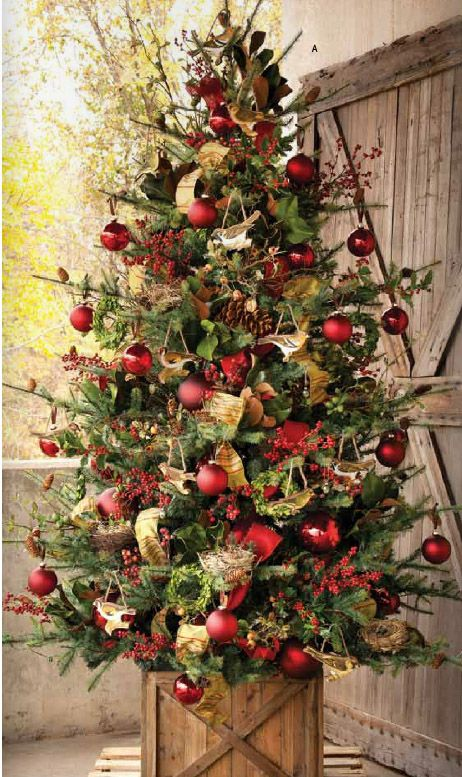 lush tree in a box with red ornaments, gold and green deco mesh and garlands