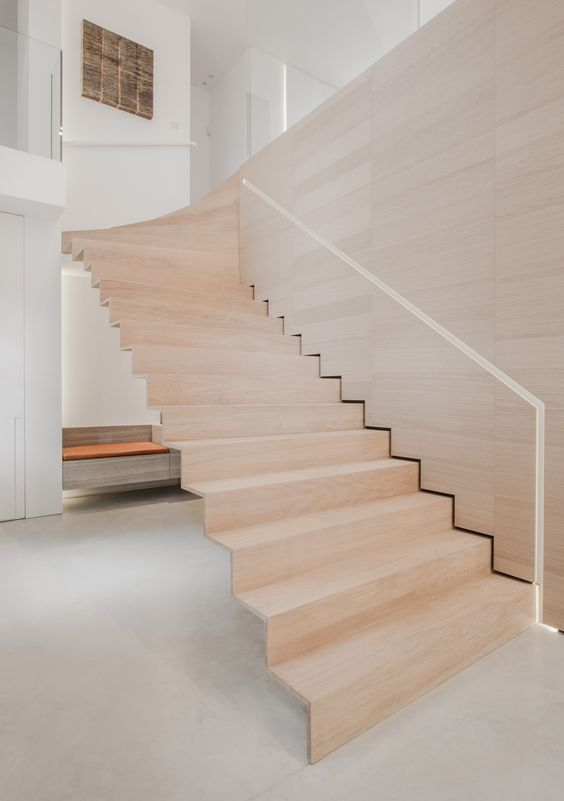 floating wooden staircase wwith a handrail cut in the plywood wall