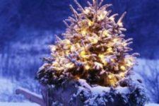 22 lighted and snowy Christmas tree in a wheelbarrow