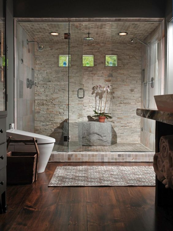 stone clad steam room with a shower and a large stone instead of a bench