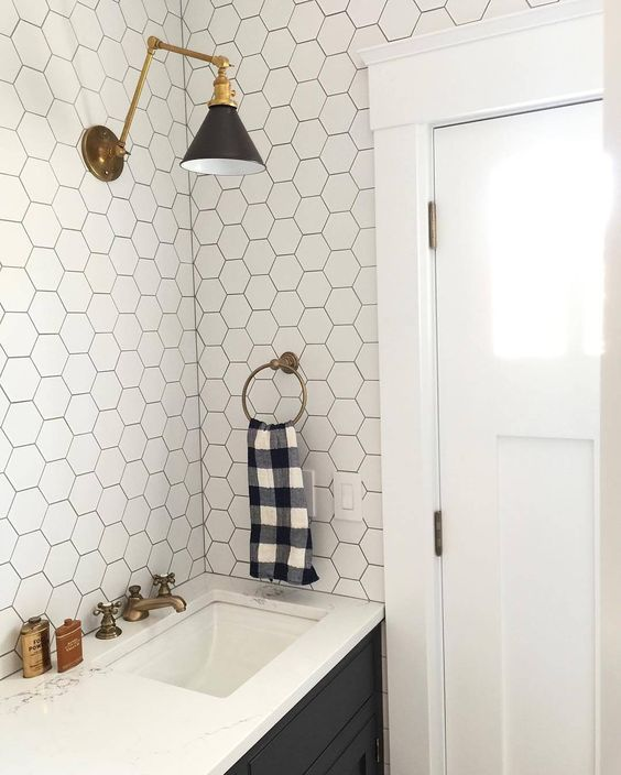 white hexagonal tiles with black grout and black cabinets