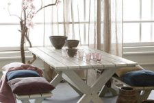 24 relaxed boho feel dining space with a whitewashed table and benches, colorful pillows