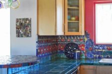 24 very bold teal tiles on the countertops and red and blue tiles on the backsplash